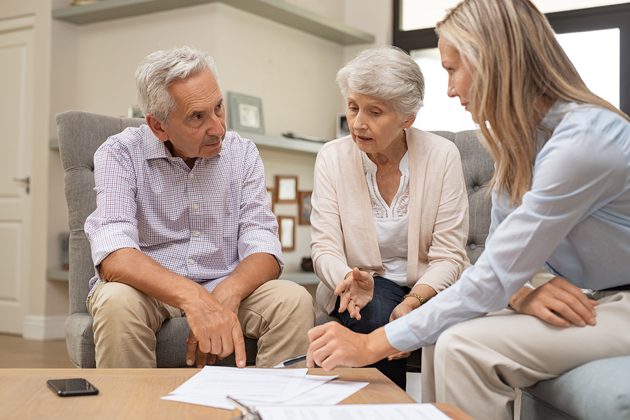 Business agent planning with a retired couple their future investment opportunities. Financial advisor talking to elderly man and woman and pointing the terms of contract on document. Retirement plans